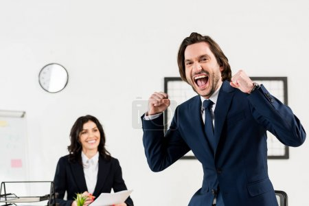 Photo for Selective focus of happy man gesturing near attractive recruiter in office - Royalty Free Image
