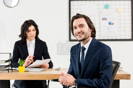 Photo for Selective focus of cheerful man looking at camera near attractive recruiter - Royalty Free Image