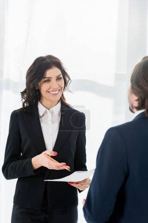 Photo pour Foyer sélectif de la femme heureuse retenant le résumé et le crayon et regardant l'homme - image libre de droit