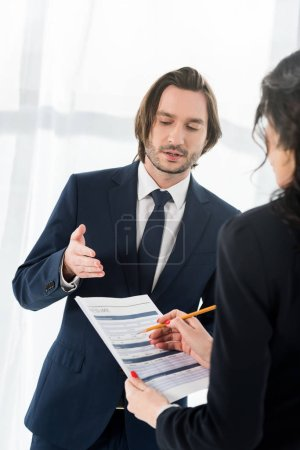 Photo for Selective focus of handsome man gesturing near woman holding resume and pencil - Royalty Free Image