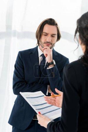 Photo pour Foyer sélectif de l'homme pensif restant près de la femme brune avec le résumé dans des mains - image libre de droit