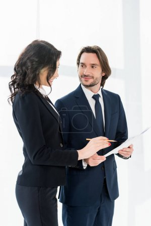 cheerful woman standing near coworker and looking at paper