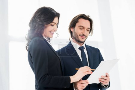 Photo pour Vue d'angle bas de la femme gaie restant près du collègue et regardant le papier - image libre de droit