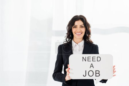 Photo for Happy and beautiful employee holding speech bubble with need a job lettering - Royalty Free Image