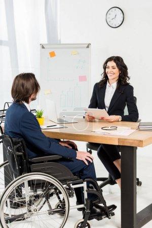 Photo pour Recruteur heureux regardant l'homme handicapé tout en retenant des documents et souriant dans le bureau - image libre de droit