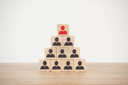 management hierarchy pyramid with wooden cubes on white