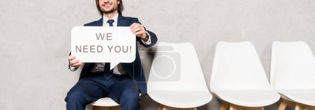 Photo for Panoramic shot of recruiter sitting on chair and holding speech bubble with we need you lettering - Royalty Free Image