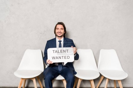 Photo for Happy recruiter sitting on chair and holding speech bubble with talent wanted lettering - Royalty Free Image