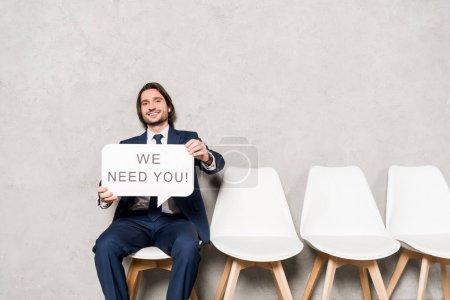 Photo pour Recruteur heureux assis sur la chaise et la bulle de la parole de maintien avec nous avons besoin de vous lettrage - image libre de droit