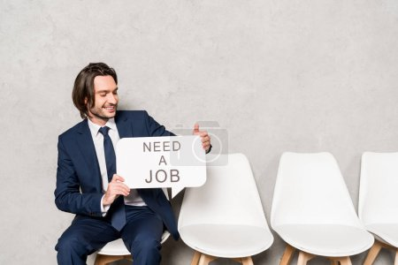 Photo for Happy employee holding speech bubble with need a job lettering - Royalty Free Image