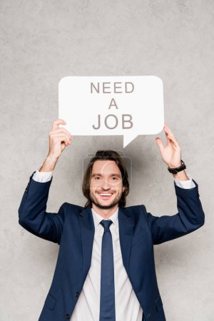 Photo for Cheerful employee holding speech bubble with need a job lettering on grey - Royalty Free Image