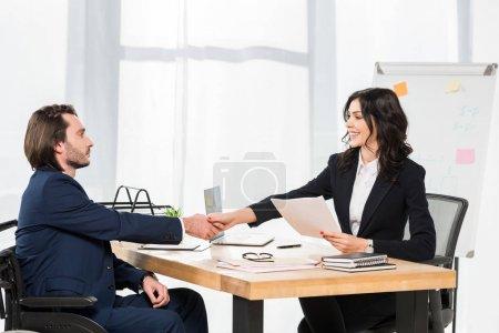 Photo pour Recruteur attrayant serrant la main avec l'homme handicapé tout en tenant des documents dans le bureau - image libre de droit