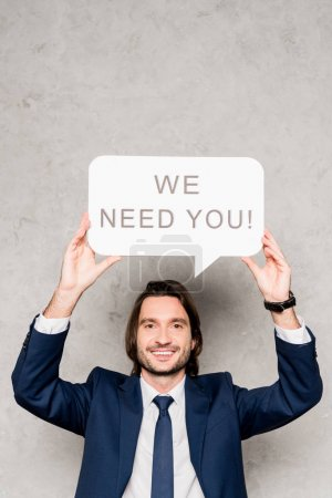 Photo for Cheerful recruiter holding speech bubble with we need you lettering on grey - Royalty Free Image