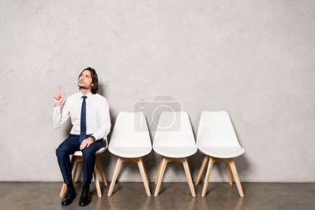 handsome man in formal wear sitting on chair and gesturing while having idea