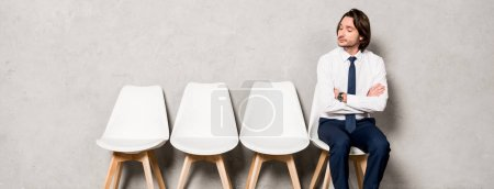 Photo for Panoramic shot of handsome man sitting on chair with crossed arms and waiting job interview - Royalty Free Image