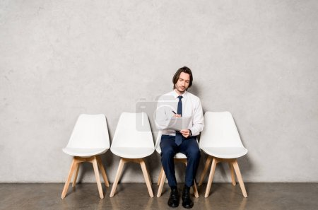 handsome man sitting on chair while waiting job interview in office