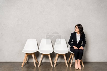 attractive brunette woman in formal wear sitting on chair before job interview