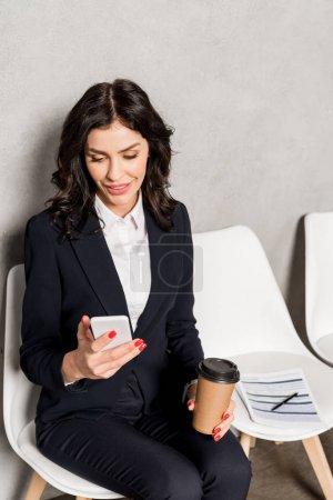 fröhliche brünette Frau mit Smartphone, während sie Pappbecher hält und auf Stuhl sitzt
