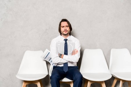 Photo for Handsome displeased man holding resume while sitting with crossed arms - Royalty Free Image