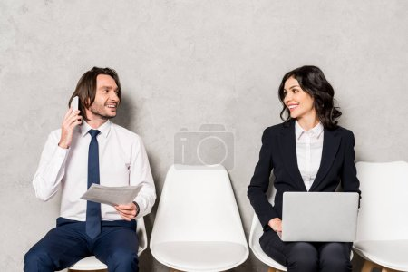 Photo for Happy man talking on smartphone and looking at attractive woman with laptop - Royalty Free Image