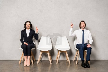 Photo for Happy brunette woman and handsome man gesturing while sitting on chairs - Royalty Free Image