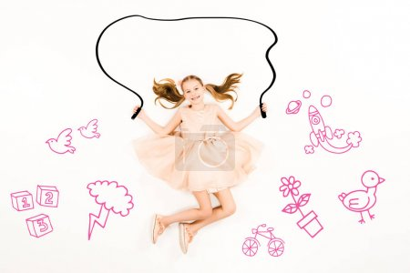 Photo for Top view of cheerful kid flying with jumping rope and smiling on white - Royalty Free Image