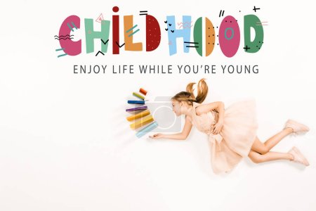 Photo for Top view of cheerful kid in pink dress holding books and flying near childhood enjoy life while you're young lettering on white - Royalty Free Image