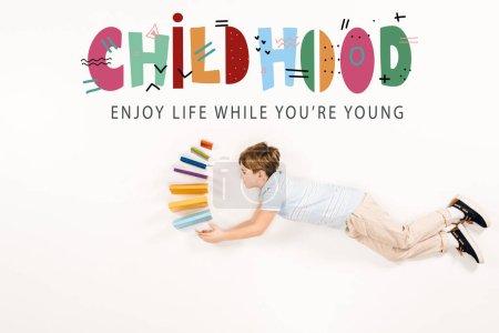 Photo pour Vue du haut de la possession de livres d'enfant et volant près de l'enfance apprécient la vie tandis que vous êtes jeune lettrage sur le blanc - image libre de droit