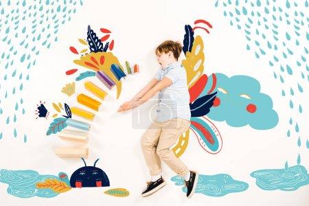 Photo pour Vue supérieure de l'enfant étonné près des livres colorés et des caractères de fée sur le blanc - image libre de droit