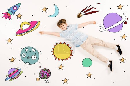 вид сверху веселого малыша, летящего в космосе на белом