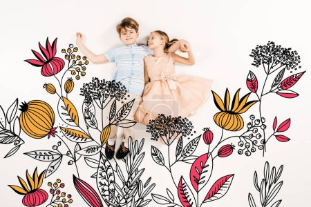 Foto de Cheerful kid looking at happy friend and lying near flowers on white - Imagen libre de derechos