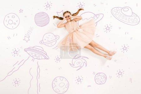 Photo pour Vue du haut de l'enfant joyeux en robe rose avec les mains près des yeux dans l'espace sur blanc - image libre de droit
