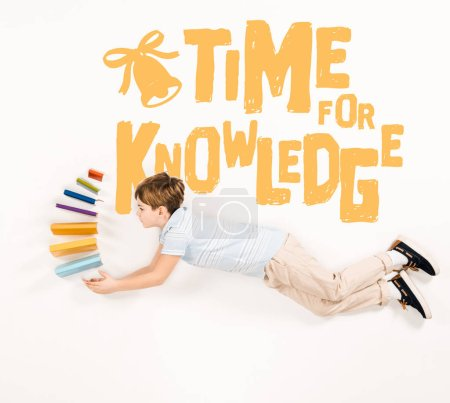 Photo for Top view of kid holding books and flying near time for knowledge lettering on white - Royalty Free Image