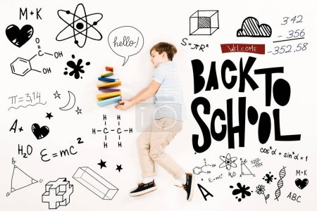 Photo for Top view of kid near colorful books and welcome back to school lettering on white - Royalty Free Image