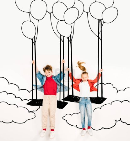 Foto de Top view of cheerful kids on swings near balloons and clouds on white - Imagen libre de derechos