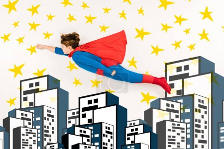 Photo for Top view of kid in super hero costume flying near stars and buildings on white - Royalty Free Image