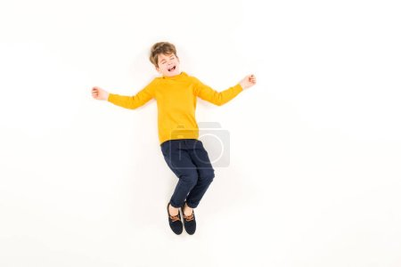 Photo pour Top view of scared kid screaming while flying on white - image libre de droit