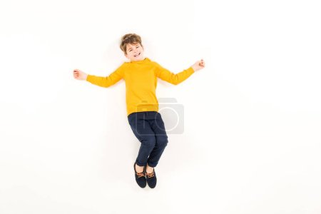 Photo for Top view of scared kid looking at camera while flying on white - Royalty Free Image
