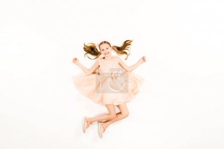 Photo for Top view of happy child looking at camera while flying on white - Royalty Free Image