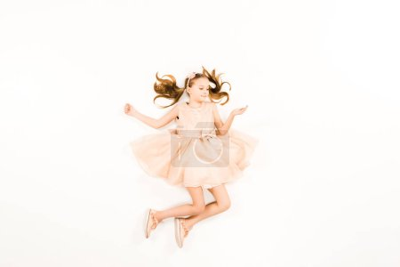Photo pour Top view of happy child in pink dress smiling while flying on white - image libre de droit