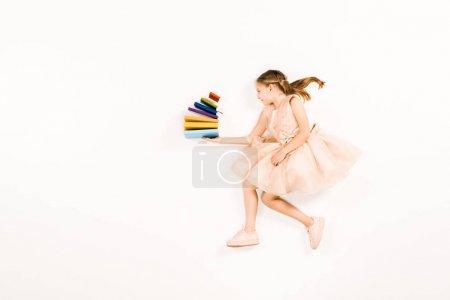 Photo pour Vue supérieure de l'enfant gai dans les livres roses de fixation de robe sur le blanc - image libre de droit
