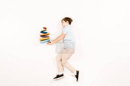 Photo pour Vue supérieure de l'enfant mignon retenant les livres colorés sur le blanc - image libre de droit
