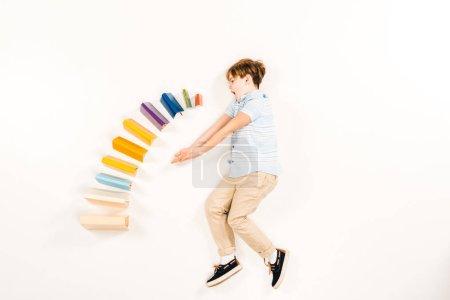 Photo pour Vue supérieure de l'enfant étonné près des livres colorés sur le blanc - image libre de droit