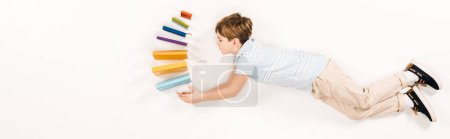 Photo for Panoramic shot of cute kid holding colorful books while flying on white - Royalty Free Image