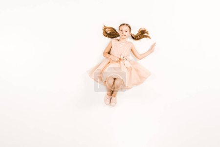 Photo for Top view of smiling kid in dress looking at camera on white - Royalty Free Image