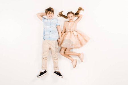 Photo pour Top view of happy kids looking at camera on white - image libre de droit