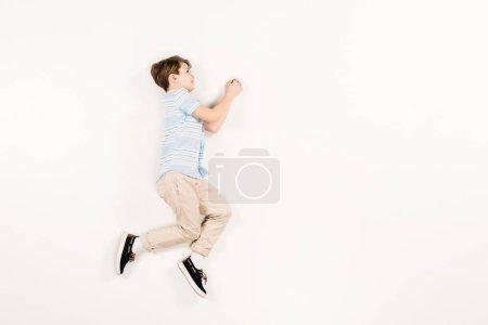 Photo pour Enfant heureux et mignon se trouvant et faisant des gestes sur le blanc - image libre de droit