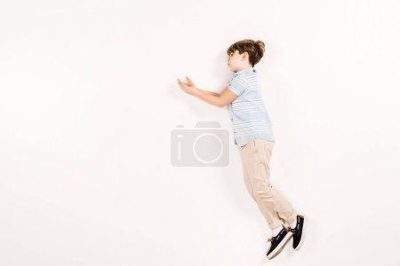 Foto de Cute child in blue t-shirt lying and gesturing on white - Imagen libre de derechos