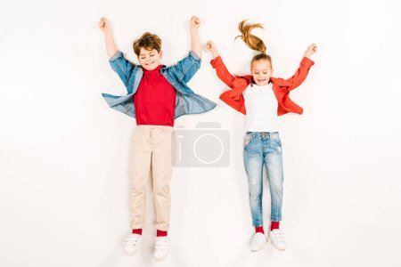 Photo pour Top view of cheerful kids with hands above head lying on white - image libre de droit