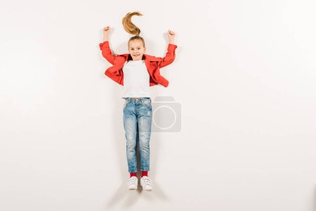 Photo pour Top view of happy kid with hands above head lying on white - image libre de droit